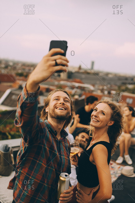 Happy man taking selfie with cheerful friends during rooftop party on terrace