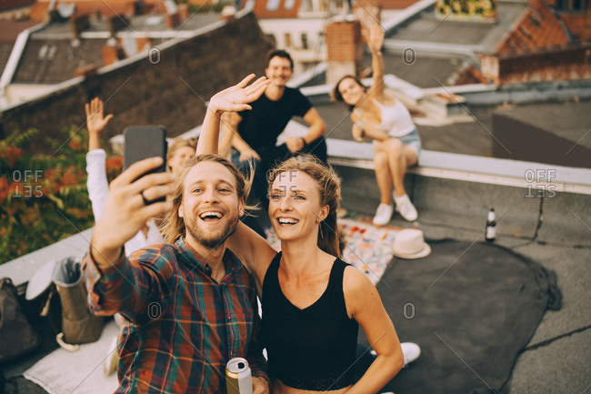 Cheerful man taking selfie with friends on smart phone while enjoying party on terrace