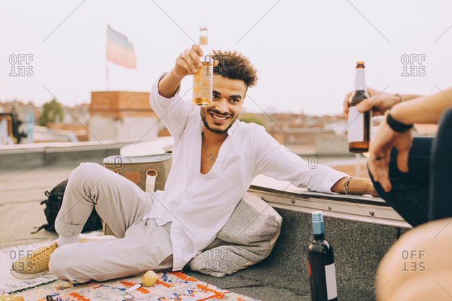 Smiling young man enjoying beer with friend on terrace at rooftop party