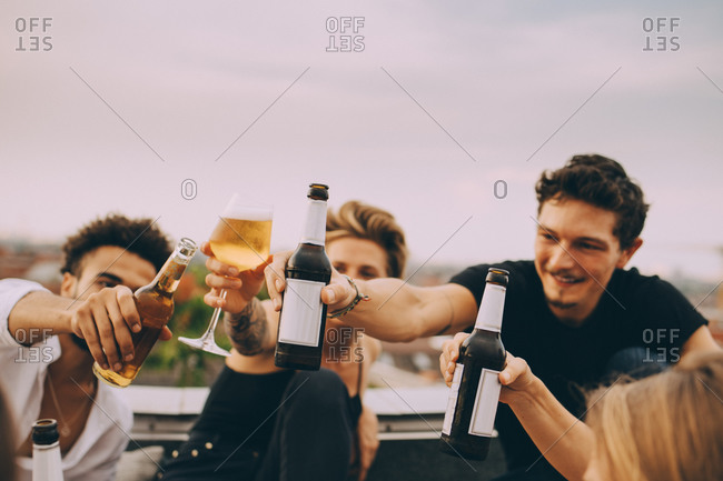 Friends celebrating with beer while enjoying in rooftop party at city