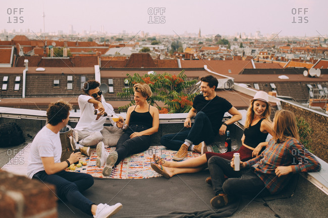 Happy friends enjoying beer while sitting at terrace during rooftop party in city
