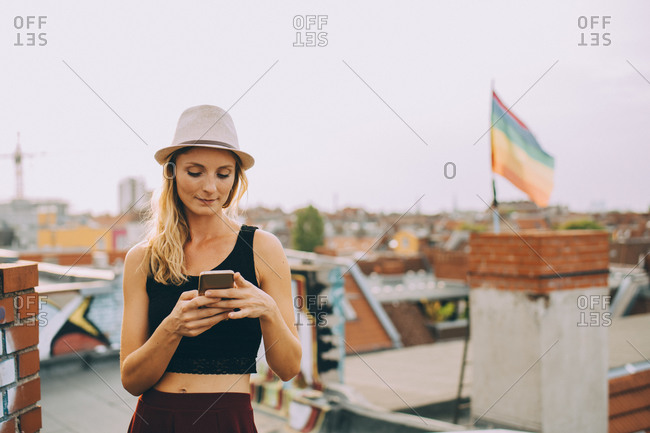 Young woman text messaging on smartphone while standing on terrace in city