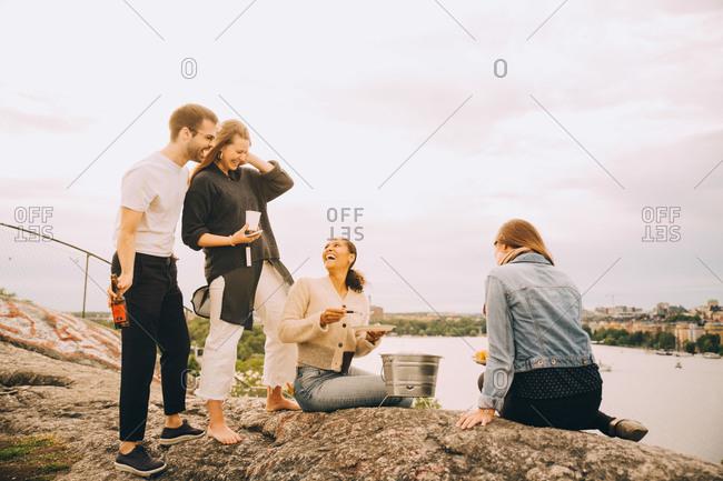 Happy friends enjoying food on lakeshore against sky