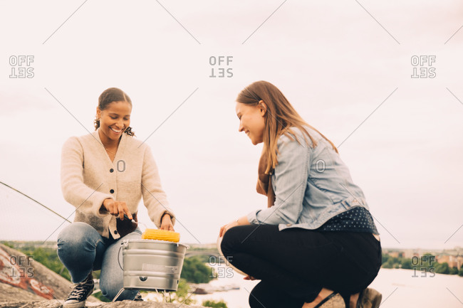 Smiling female friends roasting sweetcorns in picnic against sky