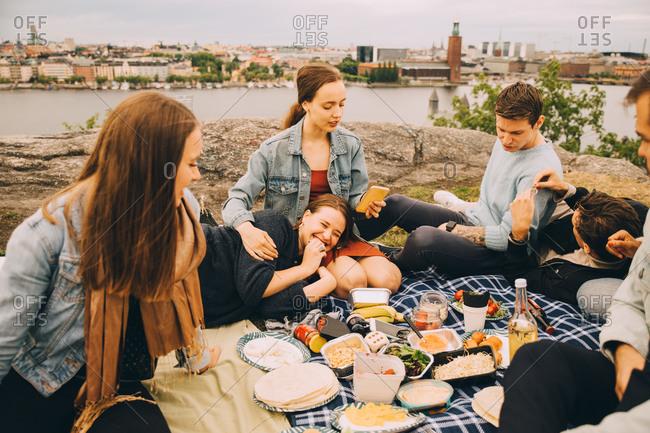 Male and female friends enjoying food on picnic blanket