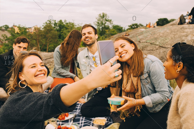 Smiling woman taking selfie with friends during picnic