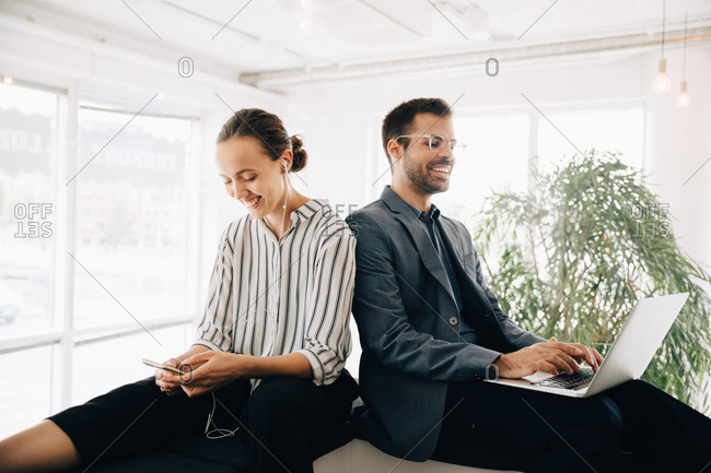 Smiling business coworkers using smart phone and laptop at creative office