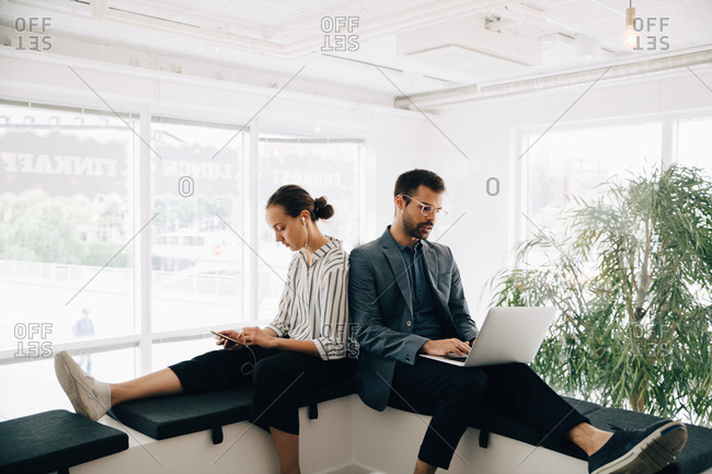 Male and female colleagues using technologies while sitting at corridor in creative office