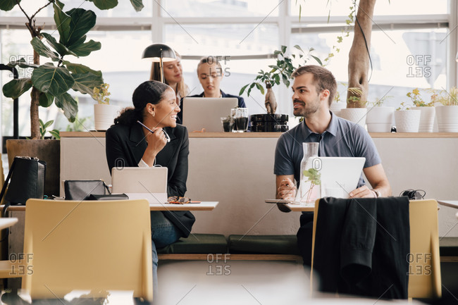 Male and female colleagues discussing while working at desk in coworking space