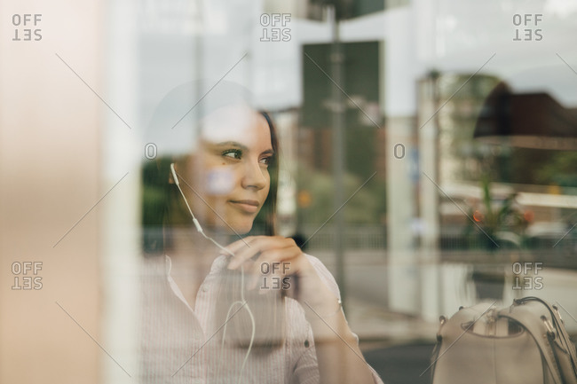 Thoughtful businesswoman wearing headphones seen through glass window at office