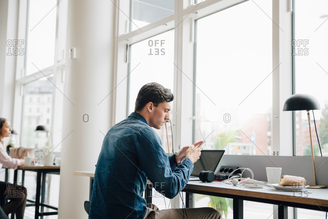 Young businessman using smart phone while sitting with laptop at desk in office