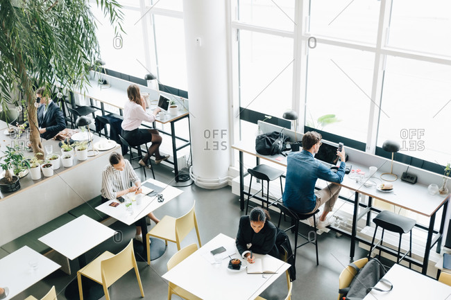High angle view of business colleagues working at desk in coworking space
