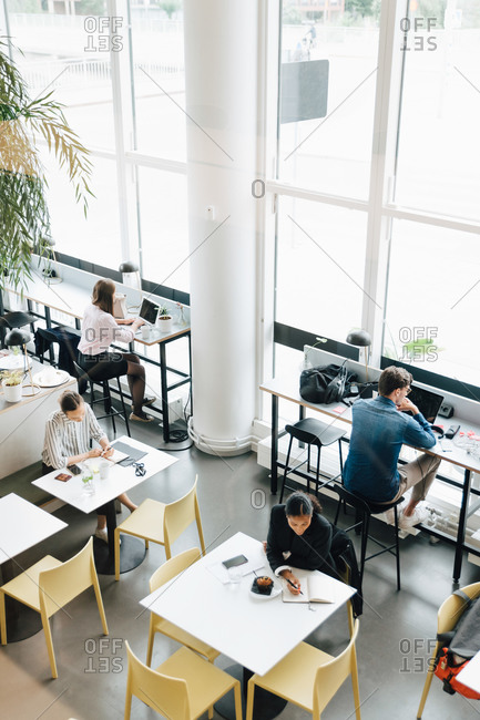 High angle view of business people working at desk in coworking space