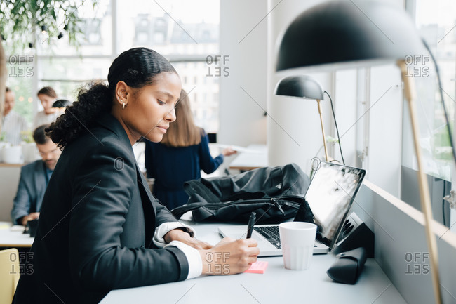 Businesswoman writing notes while working on laptop at desk in coworking space