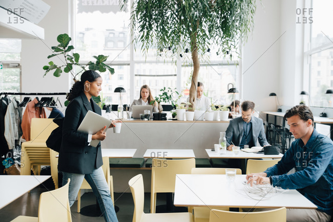 Businesswoman with laptop walking while colleagues working at desk in coworking space