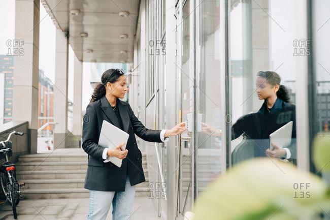 Businesswoman putting keycode to open office door