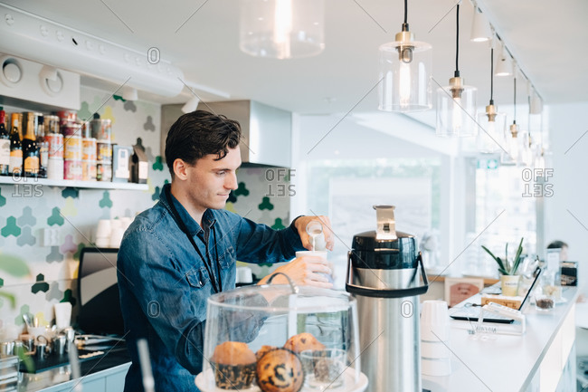 Young owner making coffee at checkout counter in office cafe