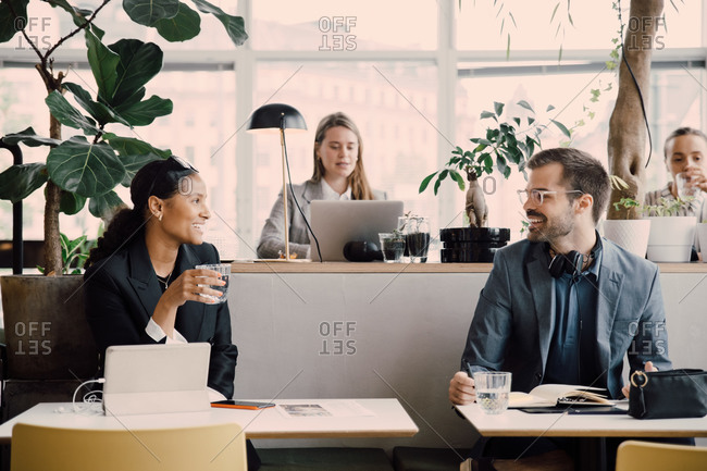 Smiling colleagues talking while sitting at coworking space