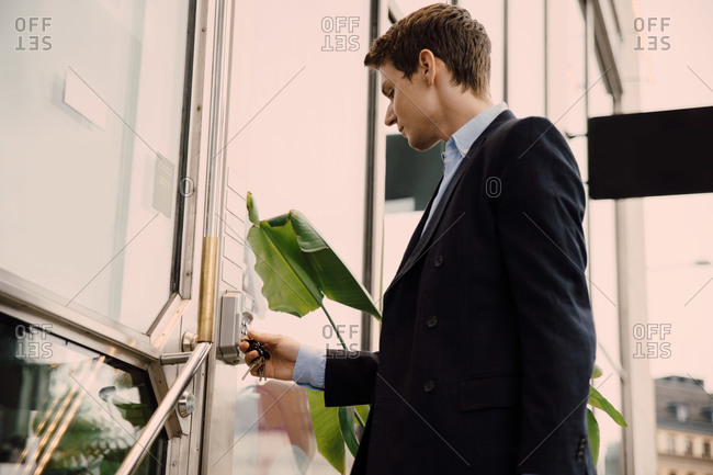 Young businessman entering keycode to open office door