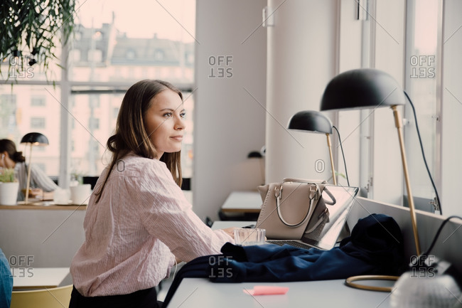 Thoughtful businesswoman sitting at desk in creative office