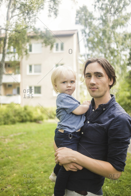 Portrait of man carrying baby boy at park