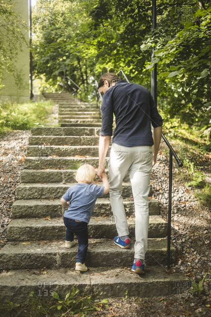 Full length rear view of father and son holding hands while moving up on steps at park