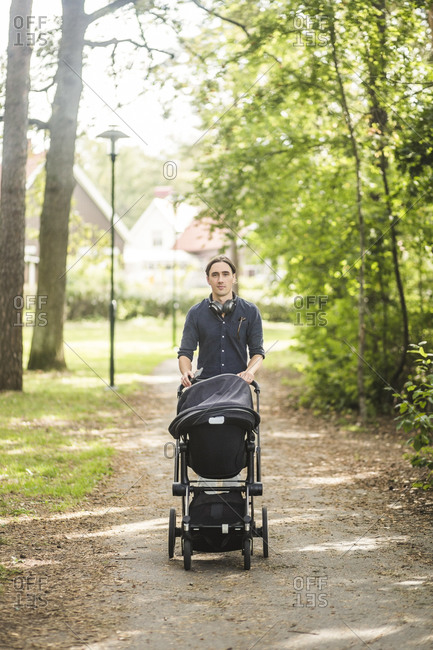 Portrait of man walking while pushing baby carriage on footpath at public park