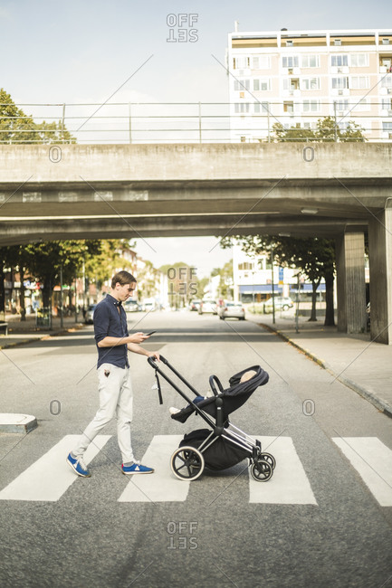 Full length side view of man using smart phone while pushing baby carriage on street in city