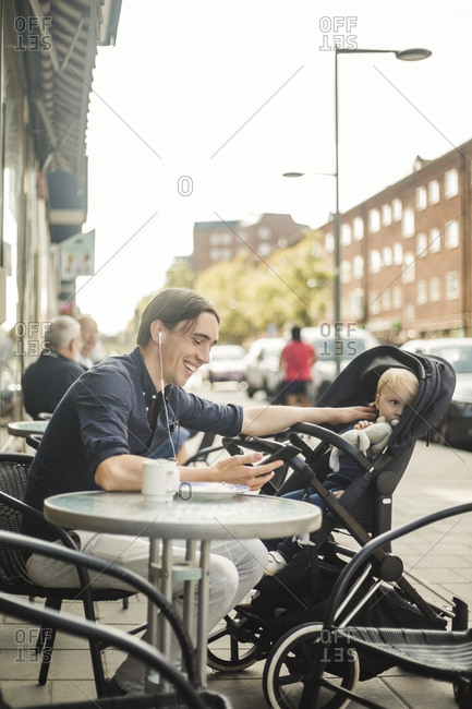 Smiling man listening music through headphones from smart phone while sitting with baby on stroller at sidewalk cafe in