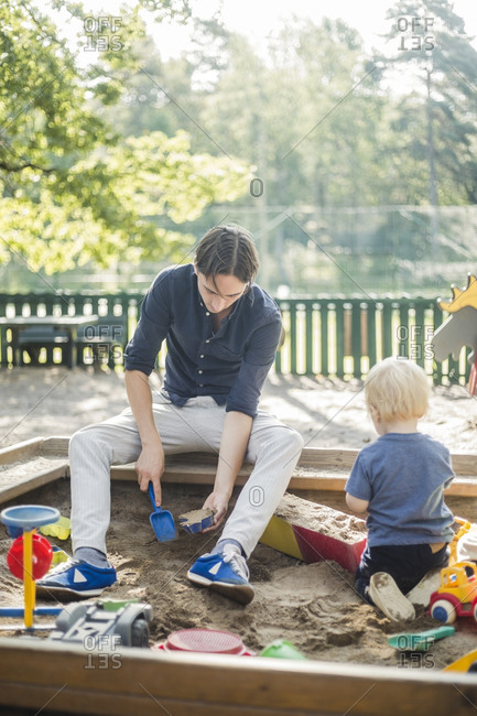 Father and son playing in playground at park during sunny day