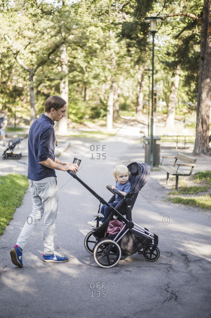 Full length of man walking while pushing son on baby carriage at public park
