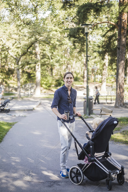 Full length portrait of smiling man standing with son on baby stroller at public park