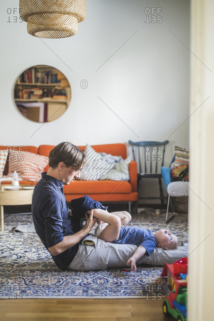Side view of man assisting toddler getting dressed in living room at home