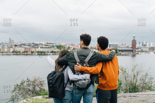 Rear view of friends with arms around standing by river in city against sky