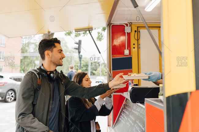 Young man standing with female friend receiving meal from food truck in city