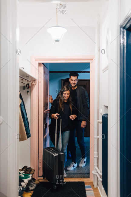 Full length of young friends standing in doorway with luggage