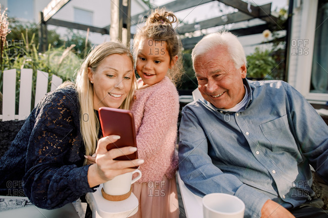 Smiling grandparent and granddaughter taking selfie with mobile phone while sitting in backyard