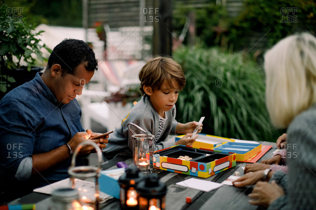 Family playing board game on table while father using mobile phone