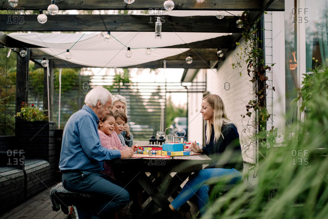Smiling family playing board game while sitting at table in patio