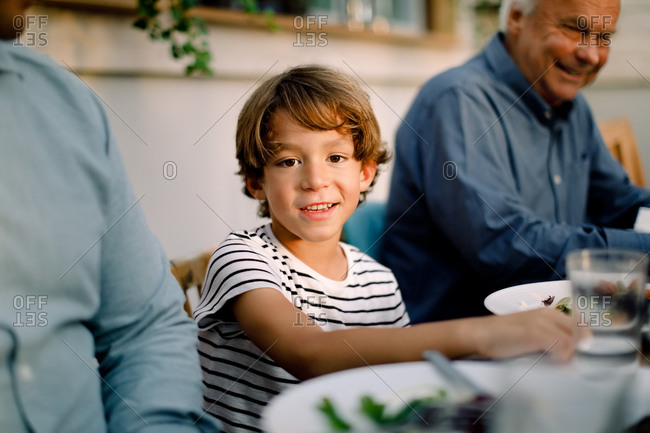 Portrait of smiling boy sitting with family at dining table during lunch