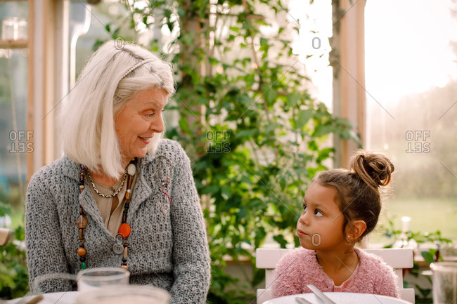 Smiling grandmother looking at granddaughter while having lunch