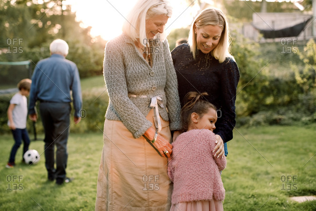 Girl embracing with mother and grandmother while standing in backyard