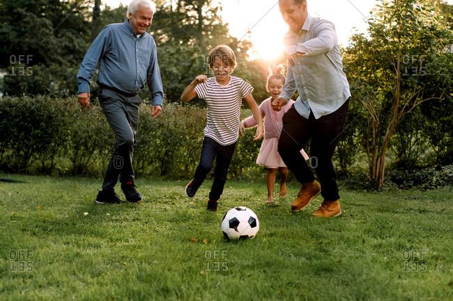 Full length of multi-generation family playing soccer in backyard