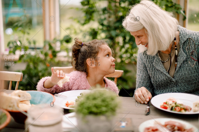 Smiling grandmother looking at granddaughter while sitting by dining table during lunch