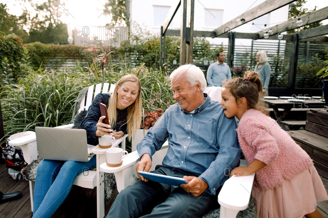 Smiling family using digital technology while sitting in backyard during weekend