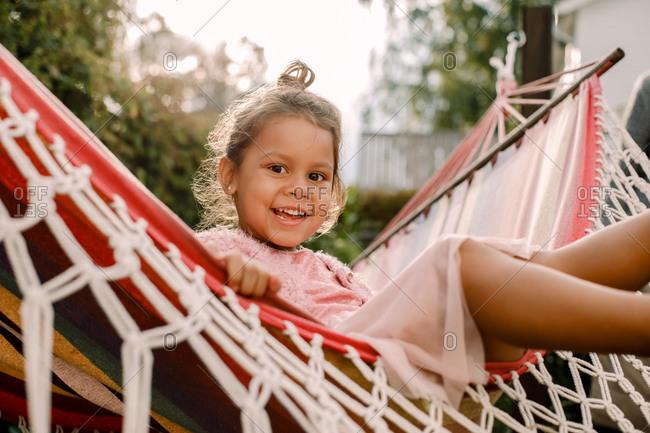 Portrait of playful girl sitting in hammock at backyard