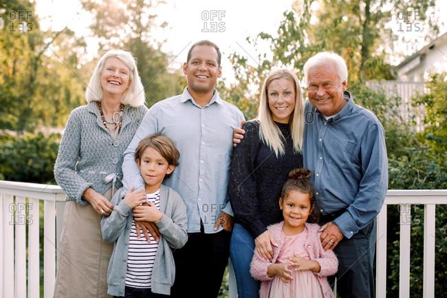 Portrait of smiling multi-generation family standing against railing in backyard