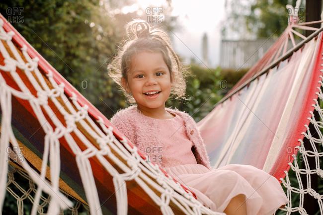 Portrait of smiling girl sitting in hammock at backyard