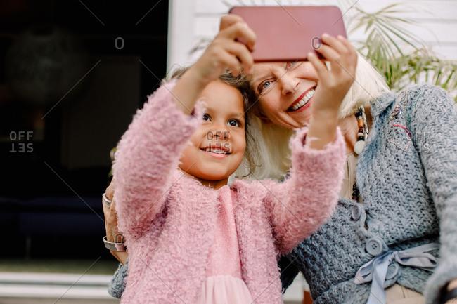 Smiling granddaughter and grandmother taking selfie in mobile phone