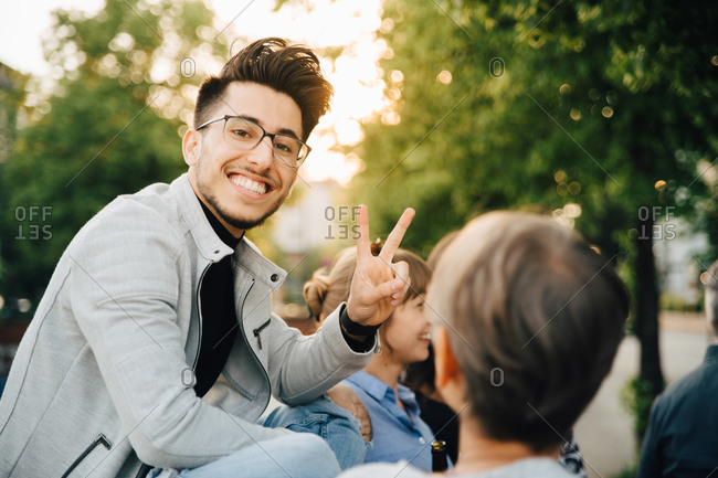 Portrait of young man gesturing while sitting outdoors